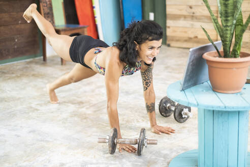 Young woman using tablet during workout at home - AMUF00022