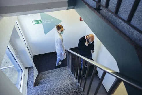 Doctor and man on the phone in staircase - MFF05247