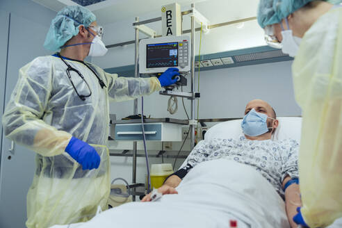 Doctors caring for patient in emergency care unit of a hospital - MFF05310