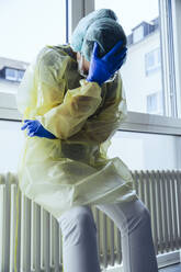 Despaired doctor wearing personal protective equipment in hospital - MFF05355