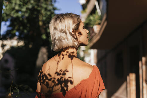 Young woman at sunlight with shadows of leaves on face and back - TCEF00360