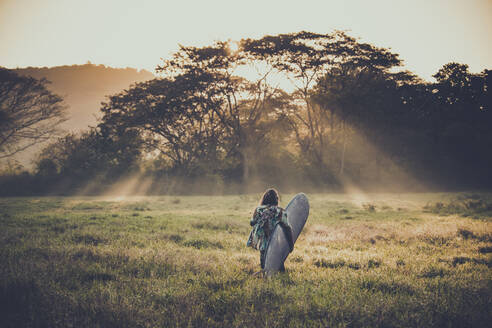 Back view of young surfer on the way to the beach at sunrise, Costa Rica - AMUF00031