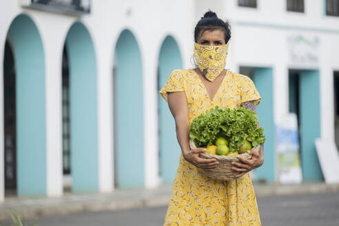 Woman wearing mouth cloth holding basket with salad and fresh fruits - AMUF00033