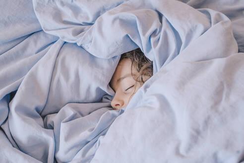 Portrait of sleeping girl lying under blanket - ERRF02959