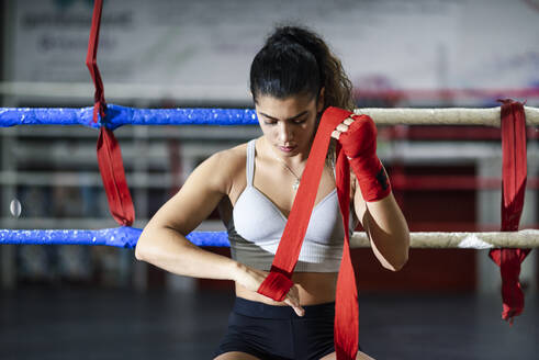Young woman tying bandage around her hand in boxing club - JSMF01493
