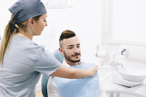 Medical secretary preparing dental treatment for patient - DGOF00603