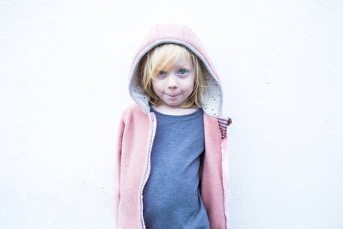 Portrait of little blond girl wearing pink hooded jacket in front of white wall - IHF00309