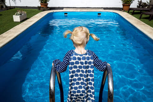 Back view of little girl with blond braids standing in front of a swimming pool - IHF00312