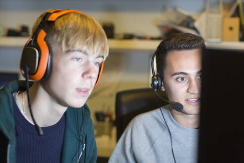 Teenage boys with headsets playing video game at computer - CAIF24956