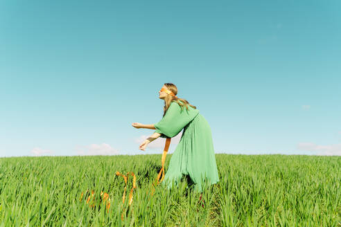 Blindfolded young woman wearing a green dress standing in a field - ERRF02984