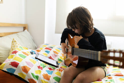 Boy sitting on bed using digital tablet for playing song on guitar - VABF02687