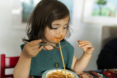 Portrait of little girl with smeared face eating pasta - VABF02729