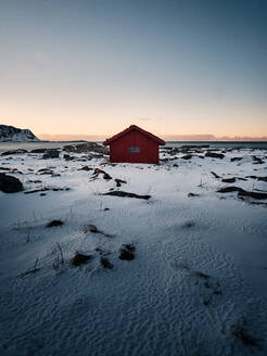 House On Snow Covered Land By Building Against Sky During Sunset - EYF02235