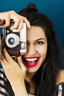 Portrait of young woman with red lips taking picture of viewer with camera - LSF00091