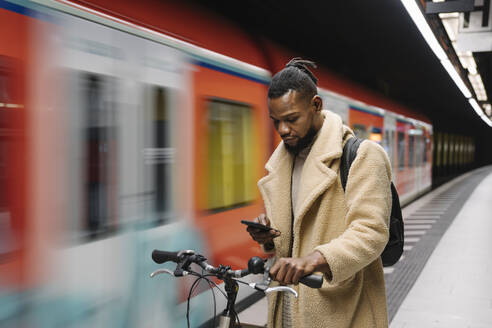 Stylish man with a bicycle and smartphone in a metro station - AHSF02112
