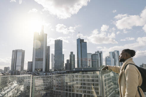 Stylish man on observation terrace looking at skycraper view, Frankfurt, Germany - AHSF02130