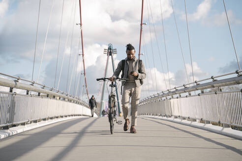 Stylish man with a bicycle using smartphone while walking on a bridge - AHSF02166