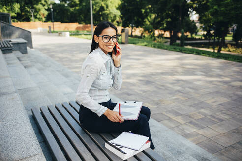 Smiling businesswoman calling and sitting on a bench in a park - OYF00115