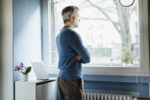 Pensive man standing in living room looking out of window - MCVF00248