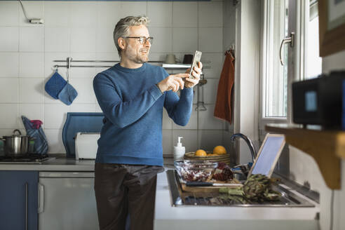 Smiling mature man standing in his kitchen taking selfie with smartphone - MCVF00257