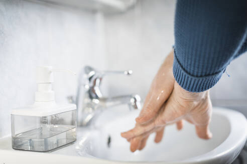 Man washing his hands with liquid soap, close-up - MCVF00263