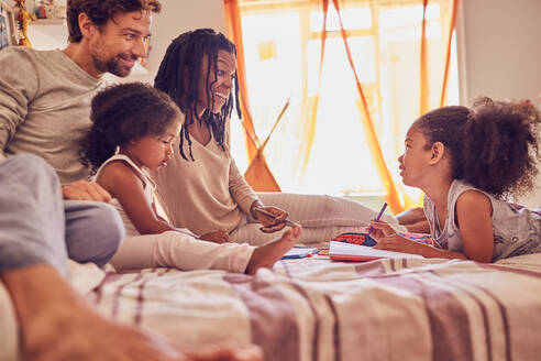 Young family coloring on bed - CAIF25511
