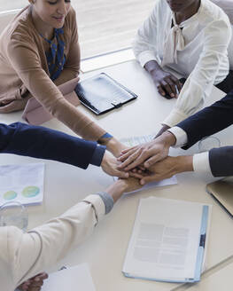 Business people joining hands in conference room meeting - CAIF25637