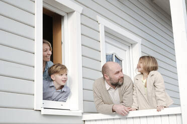 Happy family on porch of their house - VYF00123