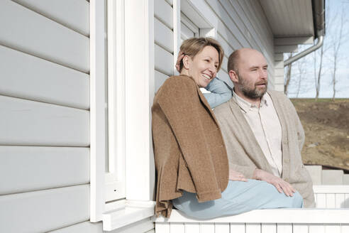 Happy couple talking on porch of their house - VYF00126