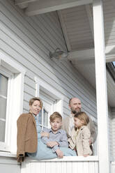 Portrait of family on porch of their house - VYF00129