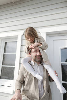 Portrait of father with happy daughter on his shoulders in front of their house - VYF00135