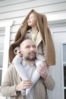 Portrait of father with happy daughter on his shoulders in front of their house - VYF00138