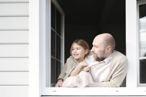 Mature man with smiling daughter looking out of window of their house - VYF00144
