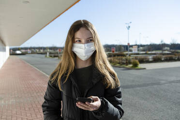 Portrait of girl wearing mask at an empty street, using smartphone - OJF00366