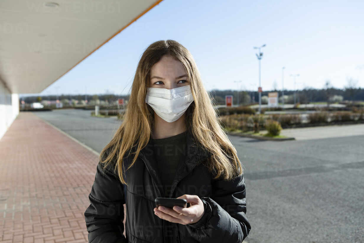 Portrait of girl wearing mask at an empty street, using smartphone - OJF00366 - Julia Otto/Westend61