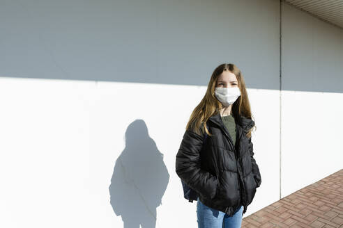 Girl with mask standing in front of a white wall - OJF00369
