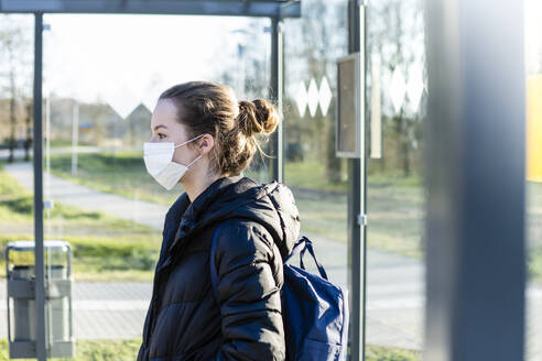 Portrait of a girl with mask waiting at bus stop - OJF00381