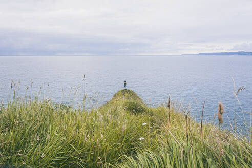 Young woman standing on grass at the cost, looking at the sea - FVSF00021