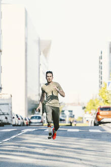 Disabled athlete with leg prosthesis exercising in the city running on a street - DAMF00295