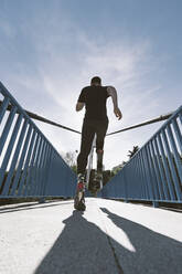 Rear view of disabled athlete with leg prosthesis running on a bridge - DAMF00307
