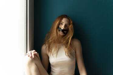 Portrait of young woman with taped mouth - AFVF05952