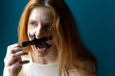 Portrait of screaming young woman pulling off sticky tape from her mouth - AFVF05955