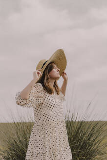 Woman with vintage dress and straw hat alone at a remote field in the countryside - ERRF03067