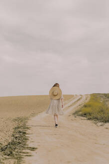 Woman with straw hat and vintage dress walking on a remote field road in the countryside - ERRF03070