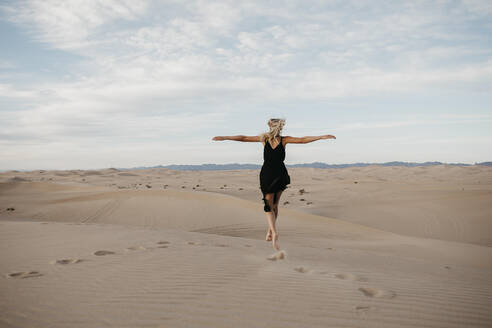 Back view of blond woman jumping in the air, Algodones Dunes, Brawley, USA - LHPF01219