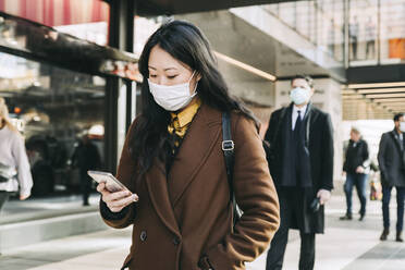 Woman with face mask walking in street using smartphone - MASF17345