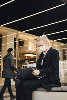 Businesswoman with face mask sitting with laptop outdoors - MASF17348