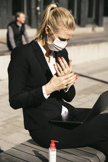 Businesswoman working with laptop waring face mask and hand sanitizer - MASF17351