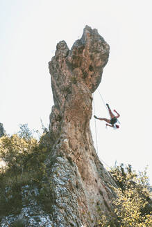 Young woman climbing rock needle in Cantabria, Spain - FVSF00042