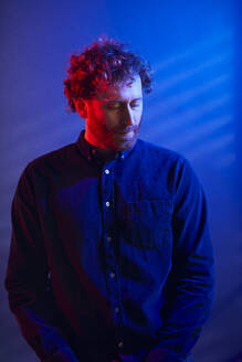 Portrait of a serious man at a blue wall - RBF07260